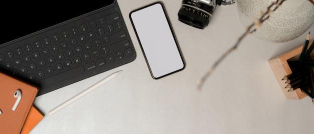Bovenaanzicht van eenvoudige werkruimte met uitknippad smartphone, kantoorbenodigdheden en kopie ruimte op marmeren tafel