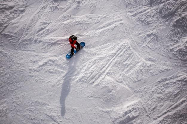 Bovenaanzicht van eenzame man op een snowboard in de winter op de berg.