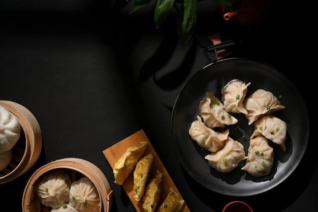 Bovenaanzicht van eettafel in chinees restaurant met dimsum op bamboestoomboot, dumplings en varkensvleesbroodjes