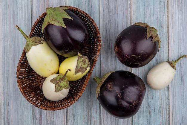 Bovenaanzicht van egglants in mand en op houten achtergrond