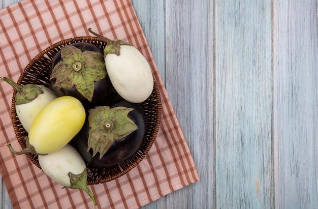 Bovenaanzicht van egglants in mand op geruite doek op houten achtergrond met kopie ruimte
