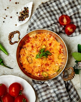 Bovenaanzicht van ei en tomaat schotel met pittige groene peper in koperen pan