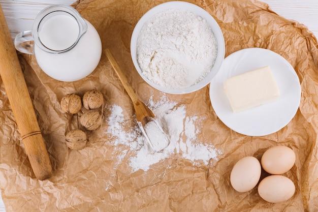 Bovenaanzicht van eieren; kaas; meel; walnoten; deegroller op bruin verfrommeld papier
