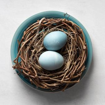 Bovenaanzicht van eieren voor pasen in vogelnest op plaat