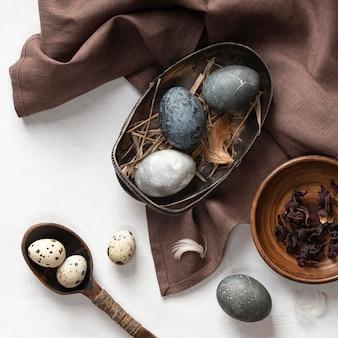 Bovenaanzicht van eieren voor pasen met stof en houten lepel