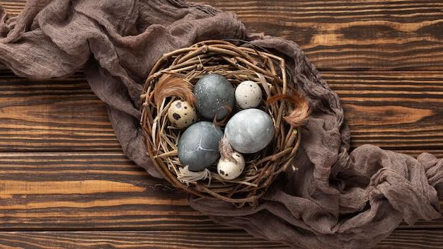 Bovenaanzicht van eieren voor pasen met stof en vogelnest