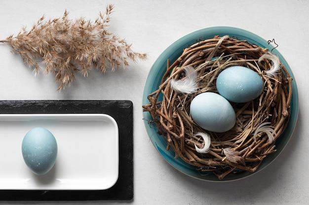 Bovenaanzicht van eieren voor pasen met vogelnest en plaat