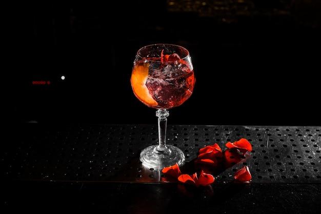 Bovenaanzicht van elegant glas gevuld met een frisse en smakelijke aperol spuit zomercocktail op de zwarte achtergrond