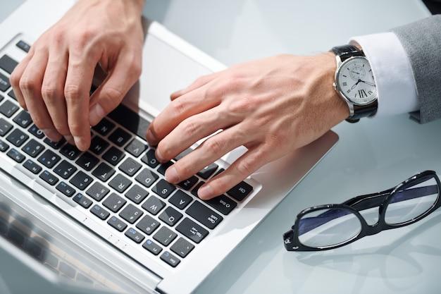 Bovenaanzicht van elegante zakenman handen op toetsen van laptop toetsenbord tijdens netwerk