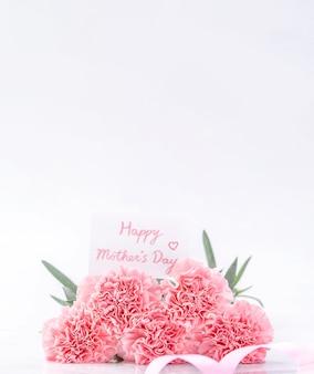 Bovenaanzicht van elegantie bloeiende zoete roze kleur tedere anjers geïsoleerd op een heldere witte achtergrond met kaart, mei moeders dag moeder groet ontwerpconcept, close-up, kopie ruimte