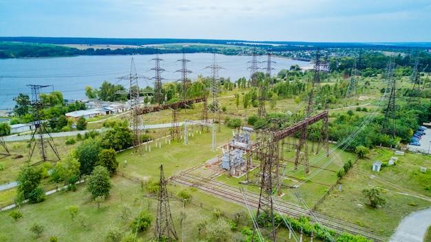 Bovenaanzicht van elektriciteitspylonen en hoogspanningsleidingen op het groene gras op de achtergrond van de rivier.