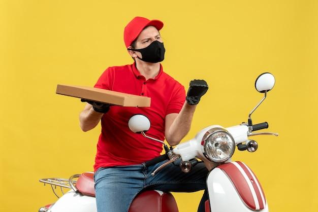 Bovenaanzicht van emotionele ambitieuze koerier man met rode blouse en hoed handschoenen in medische masker zittend op scooter weergegeven: orde