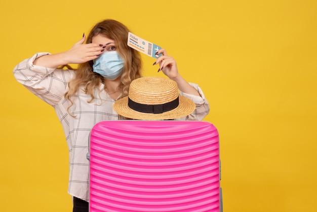 Bovenaanzicht van emotionele jonge dame die masker draagt met kaartje en achter haar roze tas staat
