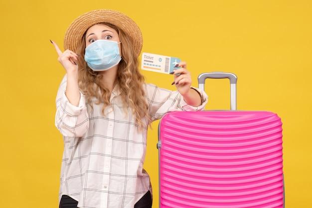 Bovenaanzicht van emotionele jonge dame met masker kaartje tonen en permanent in de buurt van haar roze tas die omhoog wijst