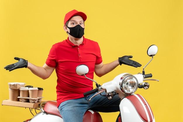 Bovenaanzicht van emotionele jonge volwassene die rode blouse en muts handschoenen in medisch masker draagt ?? die bestelling levert die op scooter zit en zich verward voelt