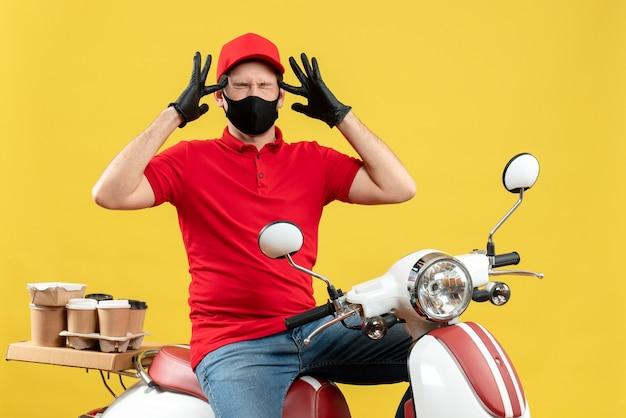 Bovenaanzicht van emotionele jonge volwassene dragen rode blouse en muts handschoenen in medisch masker leveren bestelling zittend op scooter lijden aan hoofdpijn