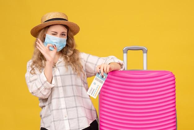Bovenaanzicht van emotionele jongedame dragen masker tonen ticket en permanent in de buurt van haar roze tas bril gebaar maken