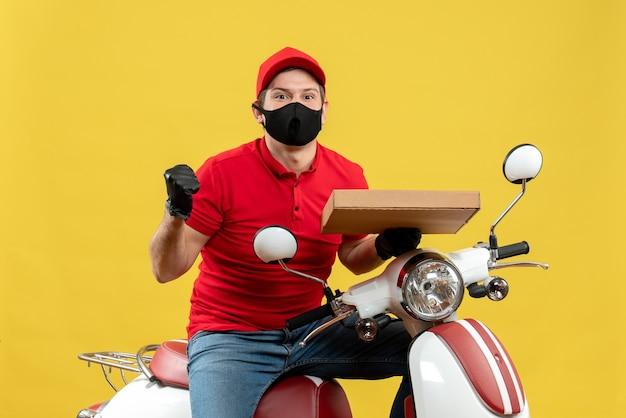 Bovenaanzicht van emotionele zelfverzekerde ambitieuze koeriersmens die rode blouse en hoedshandschoenen in medisch masker draagt dat op scooter orde toont