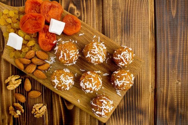 Bovenaanzicht van energieballen met gedroogde abrikozen en ingrediënten op de snijplank