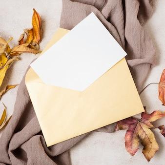 Bovenaanzicht van envelop met herfstbladeren