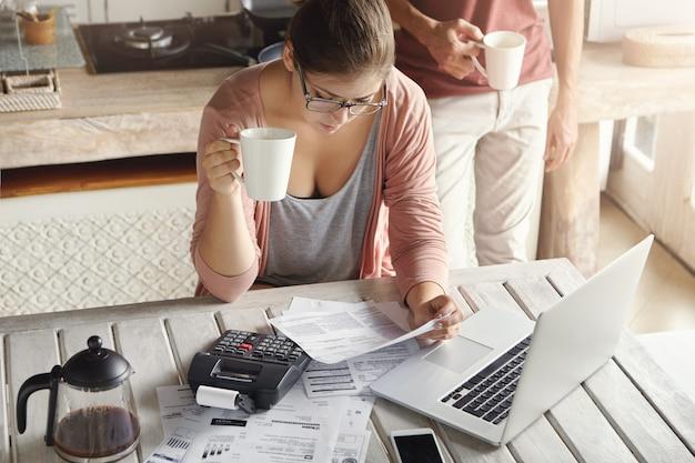 Bovenaanzicht van ernstige jonge vrouw die een bril draagt die het gezinsbudget beheert