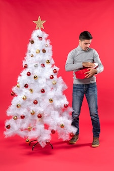 Bovenaanzicht van ernstige knappe volwassene in een grijze blouse die zich dichtbij de versierde witte kerstboom bevindt