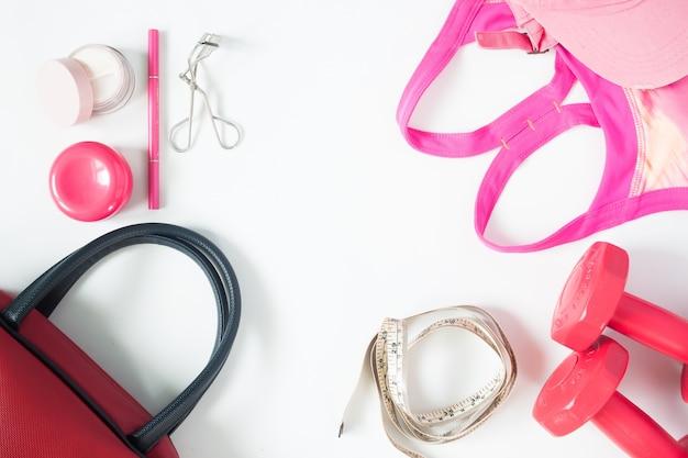 Bovenaanzicht van essentiële schoonheidsproducten, bovenaanzicht van rode dumbbells, rode handtas en sportbh, plat lege geïsoleerd op witte achtergrond