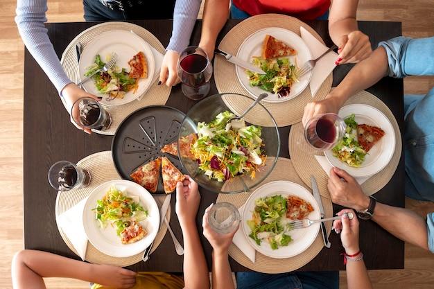 Bovenaanzicht van eten op borden en drankjes tijdens het familiediner