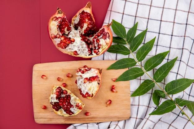 Bovenaanzicht van exotische granaatappelschijfjes met rode zaden op houten keukenbord met groen blad op gecontroleerd tafellaken op rood