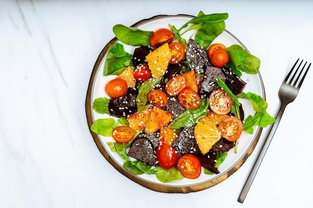 Bovenaanzicht van exquise salade van rode biet oranje cherry tomaat en rucola met olijfolie