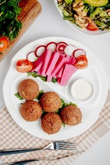 Bovenaanzicht van falafel met verse groenten op tafel