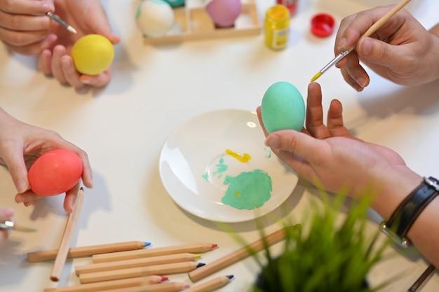 Bovenaanzicht van familie voorbereiding voor pasen festival thuis, schilderen op eieren