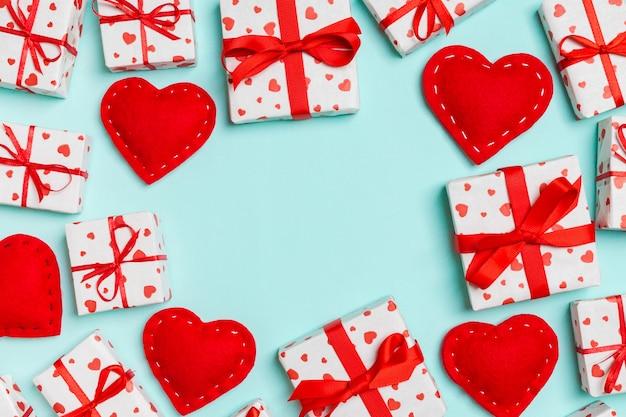 Bovenaanzicht van feestelijke geschenkdozen en rode textiel harten op tafel met kopie ruimte.