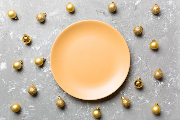 Bovenaanzicht van feestelijke plaat met gouden kerstballen op cement,