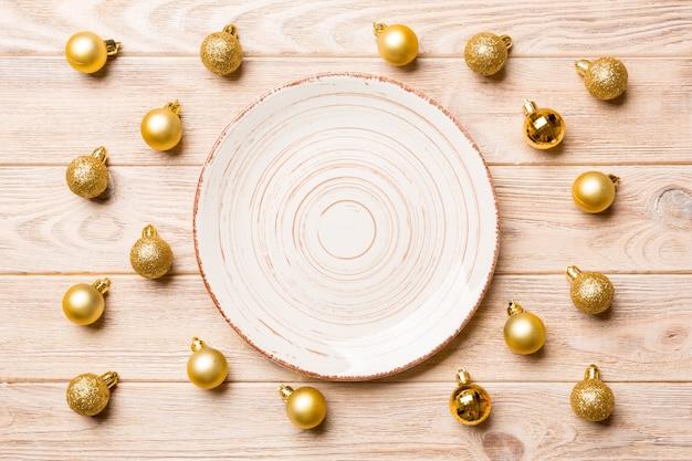 Bovenaanzicht van feestelijke plaat met gouden kerstballen op houten oppervlak