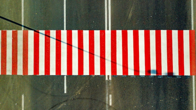 Bovenaanzicht van fel geschilderde rode en witte strepen op de weg voor het oversteken van de straat