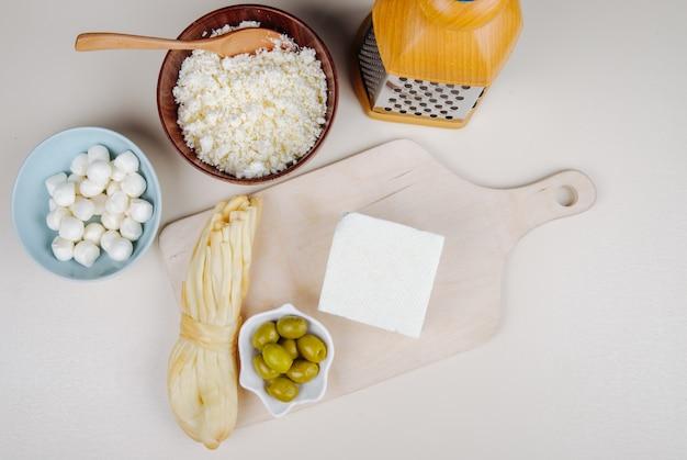 Bovenaanzicht van fetakaas met gepekelde olijven op een houten snijplank en string kaas, kwark in een kom en mozzarella met rasp op witte tafel