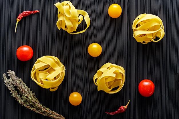 Bovenaanzicht van fettuccine met gele en rode tomaten, chili, takje tijm op achtergrond van zwarte spaghetti met inktvisinkt, voedselachtergrond