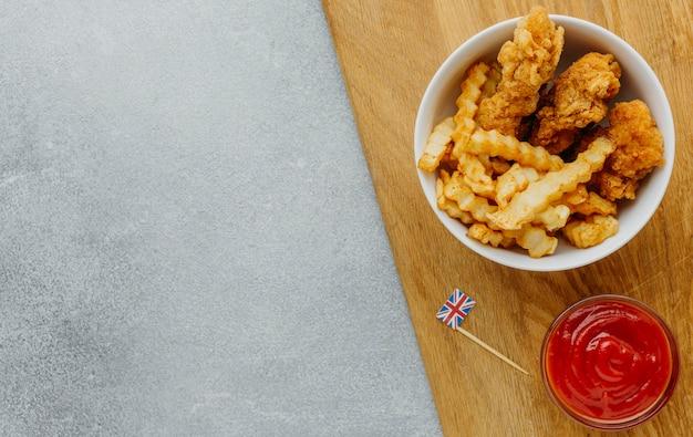 Bovenaanzicht van fish and chips in kom met ketchup en kopie ruimte