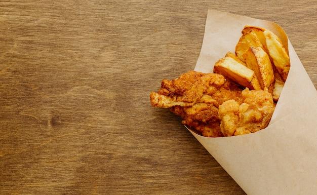 Bovenaanzicht van fish and chips in papieromslag met kopie ruimte