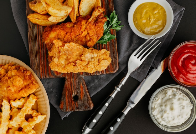 Bovenaanzicht van fish and chips met assortiment sauzen