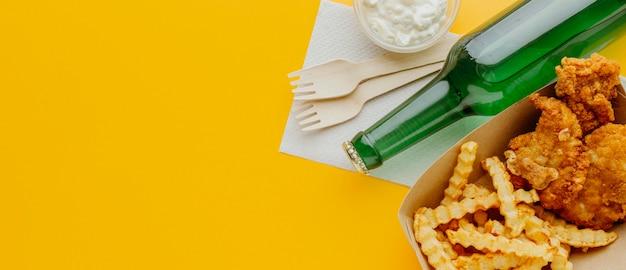 Bovenaanzicht van fish and chips met kopie ruimte en bierfles