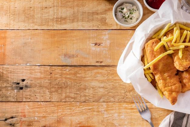 Bovenaanzicht van fish and chips met kopie ruimte en vork