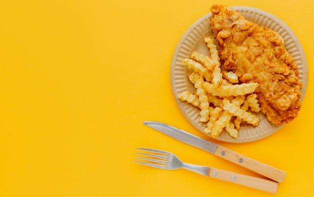 Bovenaanzicht van fish and chips op plaat met bestek