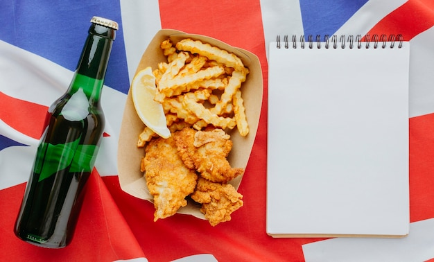 Bovenaanzicht van fish and chips op plaat met laptop en bierfles