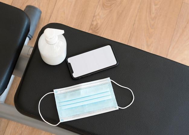 Bovenaanzicht van fitnessapparatuur met medisch masker en handdesinfecterend middel