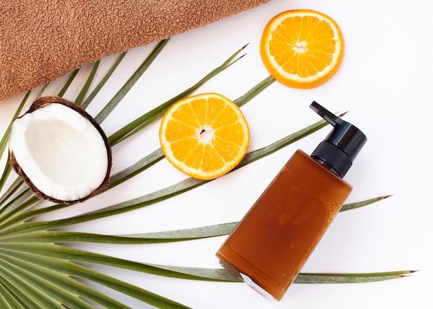 Bovenaanzicht van fles kokosnoot en orance plakjes
