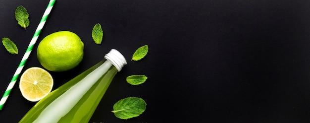 Bovenaanzicht van fles met frisdrank en limoen