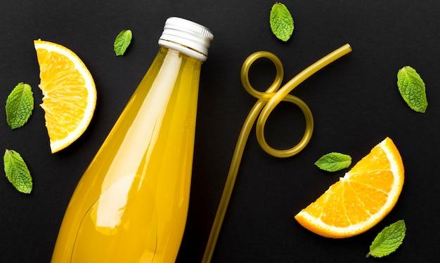 Bovenaanzicht van fles met frisdrank en stukjes sinaasappel