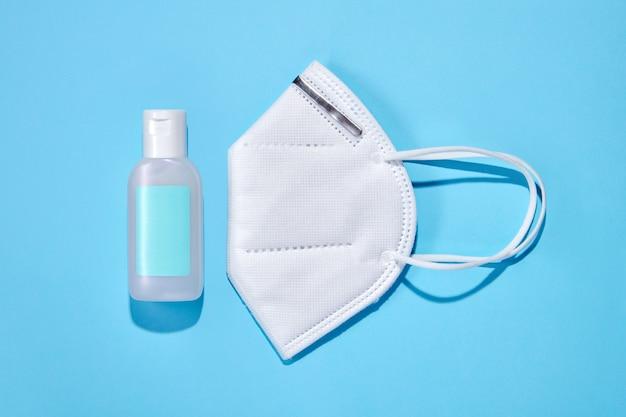 Bovenaanzicht van fles met reinigende handgel en beschermend ffp-gezichtsmasker voor coronaviruspreventie op blauw